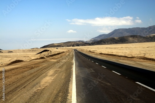 Papiers peints Route 66 Lonely asphalt road through barren waste land into endlessness of Atacama desert, Chile