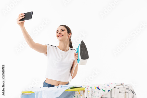 Photo of european woman housewife 20s holding mobile phone and taking selfie photo while ironing clean clothes on board