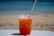 Close up of an orange & mango tropical cocktail overlooking a beautiful blurred beach setting background.