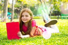 Cute Little Blond Girl Reading Book Outside On Grass