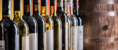 Fototapeta Wine bottles in row and oak wine keg. obraz