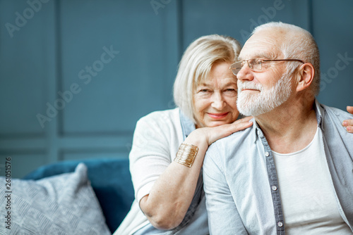Slika na platnu Portrait of a beautiful senior couple embracing each other, sitting on the couch
