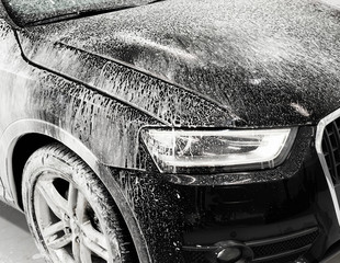 Washing black car with active foam, car wash with soap