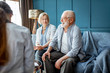 Senior couple sitting with nurse during the medical consultation in the comfortable office