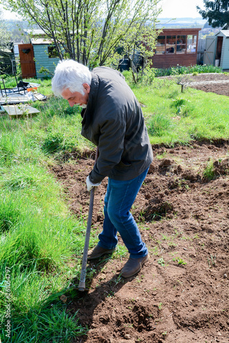 Photo Man preparing ground to grow own vegetables in an allotment garden