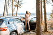 Young woman traveler enjoying nature while traveling by car in the picturesquare forest with lake