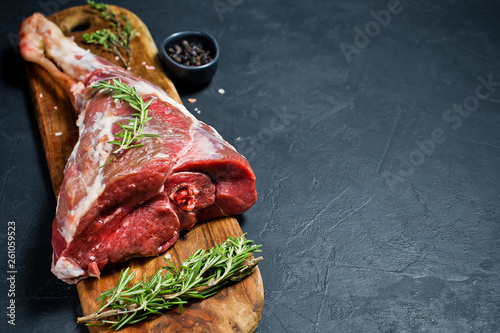 Fotografiet A raw leg of lamb on a wooden chopping Board