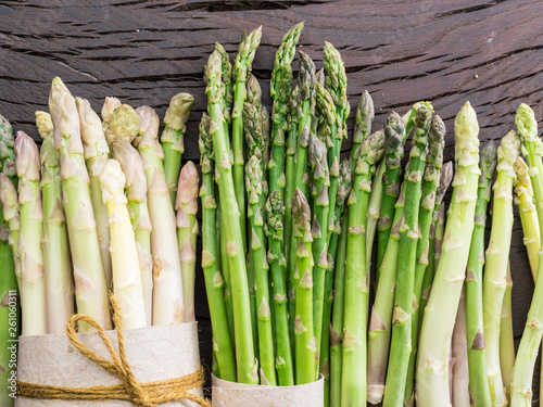 Green and white types of asparagus sprouts on wooden table Canvas Print