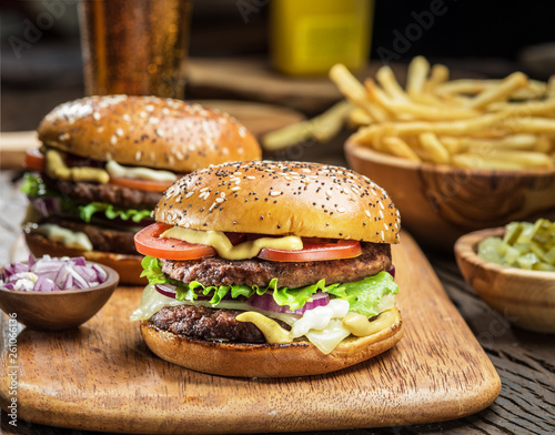 Canvas Print Hamburgers and French fries on the wooden tray.