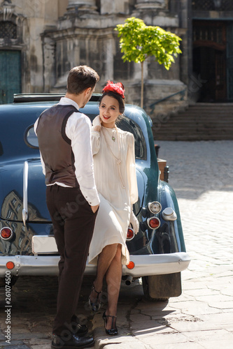 Fotografia  Man holds woman dressed in 30s style tender standing on the old street