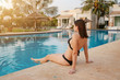 summer holidays in luxury hotel, woman relaxing near beautiful swimming pool