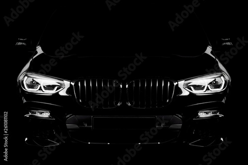 Sylwetka czarny samochód sportowy z reflektorami na czarnym tle.