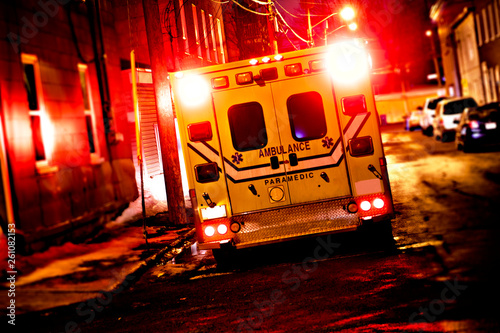 An ambulance car parked on the side street at night Canvas Print