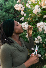 Female Smells Flowers While Trimming Them