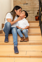 Young Mom Giving A Kiss On The Cheek To Her 4 Year Old Son Sitting On The Steps Of His House