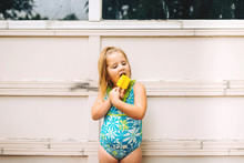 Toddler Girl Eating A Yellow P...