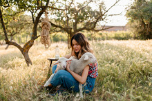 Farm Girl Cuddling With Lambs