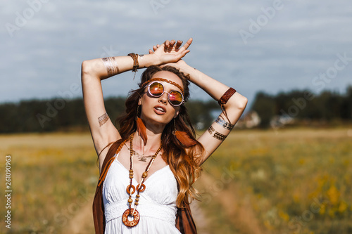 Платно Pretty amazing free red-haired hippie girl dancing outdoors, feathers and braids