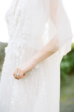 A Bride In A Delicate Embroidered White Wedding Gown & Veil Draping Gently Holds Her Gown