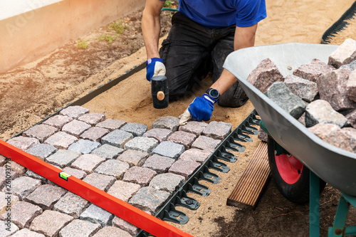 Fotografie, Obraz pathway construction - man laying stone pavers at home backyard