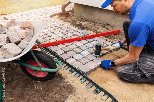 worker laying granite cobblestone pathway around the house Canvas