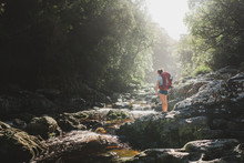 Hiker Crossing A River In A Forest.