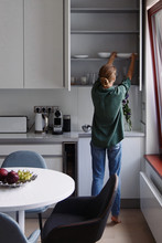 Woman Taking Dishes From Cupboard
