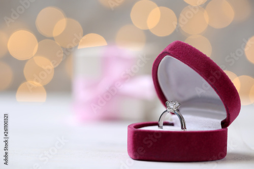 Fotografia, Obraz Box with ring on table against blurred lights. Space for text