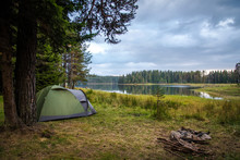 Camping Near A Lake In A Cloudy Day - Tent And A Fireplace Near A Lake.