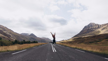 Woman Jumping On Highway In Iceland