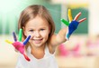 Cute little girl with colorful painted hands on class background
