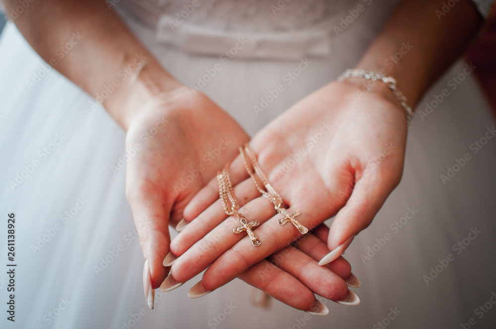 Fototapeta Bride holding gold christian crests in the hands
