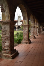 San Juan Capistrano, CA., U.S.A. Ap. 21, 2018. Mission Courtyard, Fired Red Brick Pillared Portico, Fountains & Water Lilies, Packed Dirt, Flat Red Brick-set Paths, Beautiful Palms, Trees & Floral