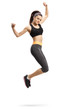 Happy young female in sportswear jumping