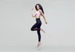 Amazing woman in trendy sportswear jumping. Smiling beautiful slim brunette young girl in fashion leggings and pink top expressing happy emotions. Gray background. Sport, fitness, lifestyle concept.