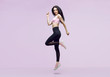 Woman in trendy sportswear jumping. Smiling beautiful slim brunette young girl in fashion leggings and pink top expressing happy emotions. Purple background. Sport, fitness, lifestyle concept.