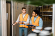 selective focus of handsome worker opening door near indian colleague