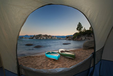 A View Through A Tent Door Of Two Paddle Boards Sitting On A Beach.
