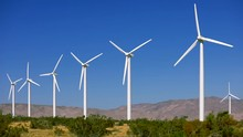 Clean And Green Energy Equipment Within Beautiful Scenic Landscape. Row Of Wind Turbines On The Hilltops Viewed Across Rolling Agricultural Land.