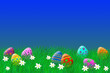 canvas print picture - Colorful easter eggs laying in the grass under a blue sky