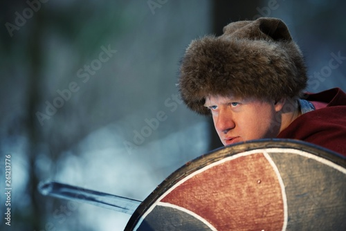 Fotografiet  Man dressed as a medieval warrior takes refuge behind a shield and holds a sword in his hand