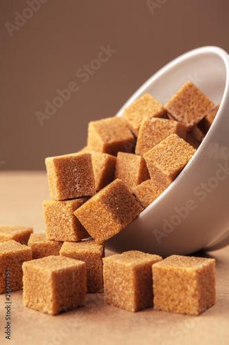 Fotografie, Obraz  Brown cane sugar cubes on a light brown background
