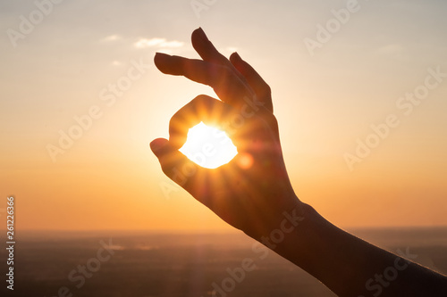 Obraz hand sign and sun rays going through hands at sunset - fototapety do salonu