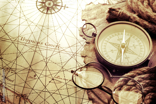 Fotomural  Vintage compass and glasses on antique map