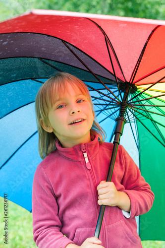 Fototapeta Little girl standing under umbrella in a rain outdoors