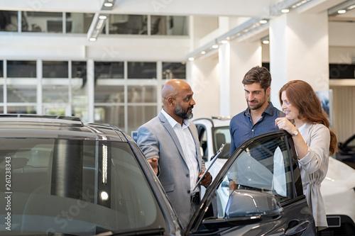 Fototapeta Couple examining new auto with car dealer