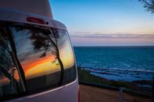 Reflection Of Tree Silhouettes On Camper Van Window In Front Of Indian Ocean In Australia