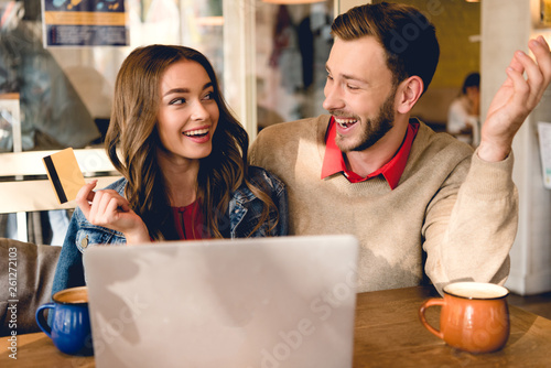 Keuken foto achterwand Eigen foto cheerful young woman holding credit card and looking at man near laptop
