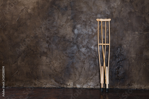Tela wooden crutches on the  grungy wall.
