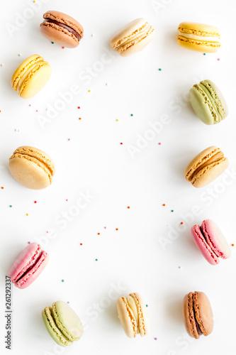 Aluminium Prints Macarons sweet dessert frame with macarons on white background flat lay mockup